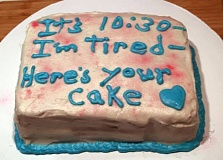 A funny cake picture about a tired mom and a youngest kid's birthday cake.