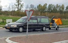 A Funny car picture of a hearse pulling a chipper