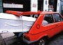 Funny Pictures of White Casket Sticking Out of Small Red Car