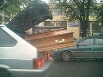 A casket sticking out of a car.