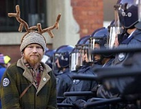 Picture of protestor with antlers and riot squad